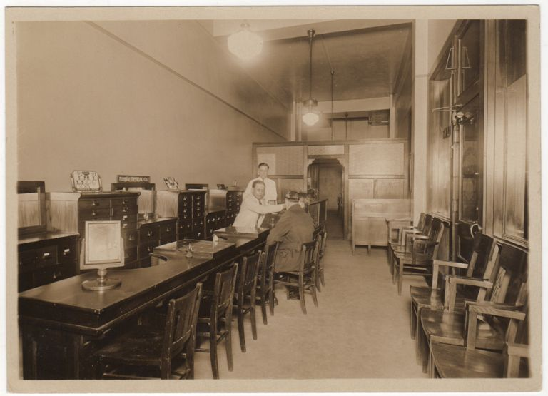 A photograph of the interior of the Optical Service Company as well as the proof copy of an advertisement for the business that was published in the St Louis Post-Dispatch. Unknown photographer.