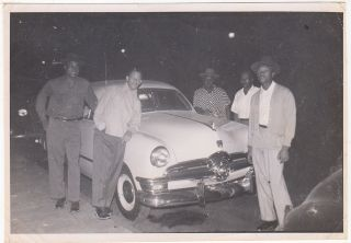 Photograph showing a group of five young African-American men posing with what appears to be a brand new 1950 Ford Tudor sedan. Unknown photographer and subjects.